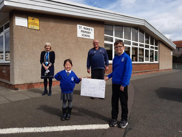 From left: St Marie's RC Primary headteacher Mary Caldwell with janitor George Tullis who retired on Wednesday along with pupils Charlene Ho (5) and Kenzi Mackie (10) with a special poster to mark George's departure.