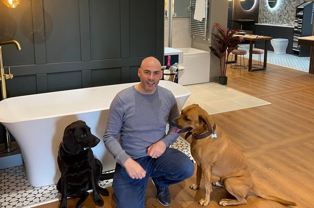 Sean Brown in his new showroom with his two dogs.