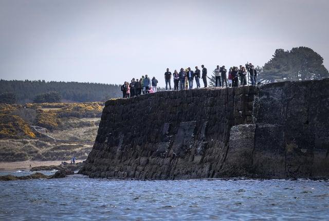 Люди смотрят со стены гавани, как молодые моряки из Гордонстоуна возлагают венок.