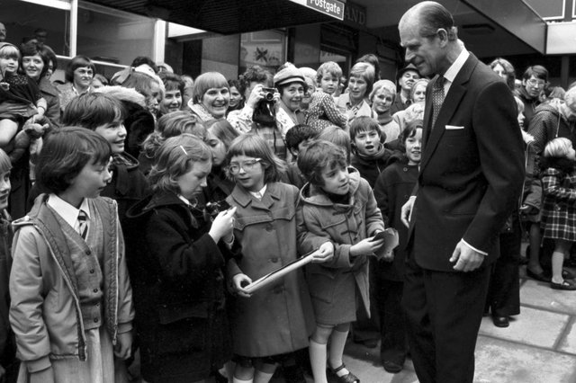 October 1976: Prince Philip  stops to chat with a little girl whose camera isn't working when he visits the Kingdom shopping centre in Glenrothes.