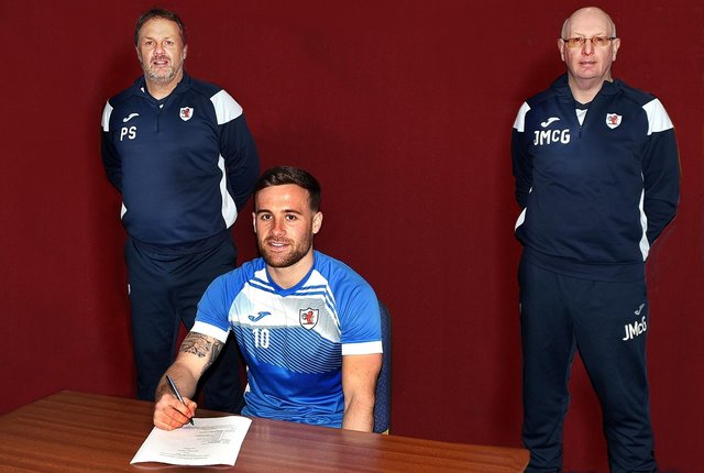 Lewis Vaughan signs his contract extension with Rovers assistant boss Paul Smith and manager John McGlynn