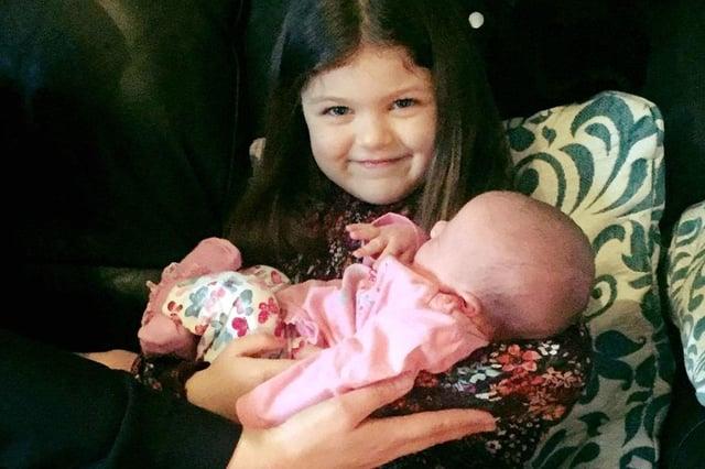 Kara McMillan holding Robyn as a baby
