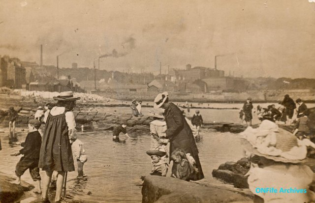 People paddling in the Bucket Pats on the Kirkcaldy shore around 1900.  The Bucket Pats were pools that had been used in the salt industry to collect sea water so that salt making could continue when the tide was out