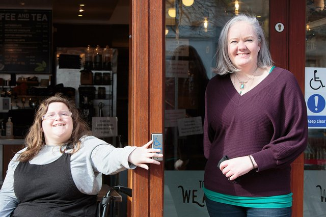 Erin Watson (left) and Zest owner Lisa Cathro try the new disabled push pad on the front door.